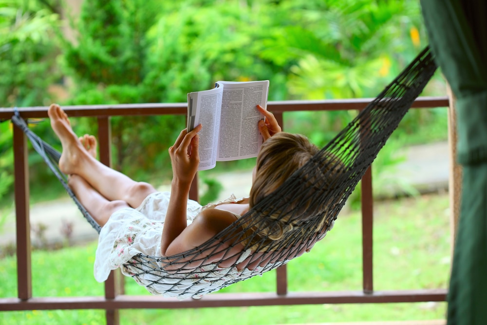 Procrastination - woman relaxing in a hammock